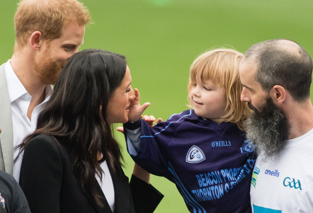 Meghan Markle and Prince Harry bonding with a little kid.