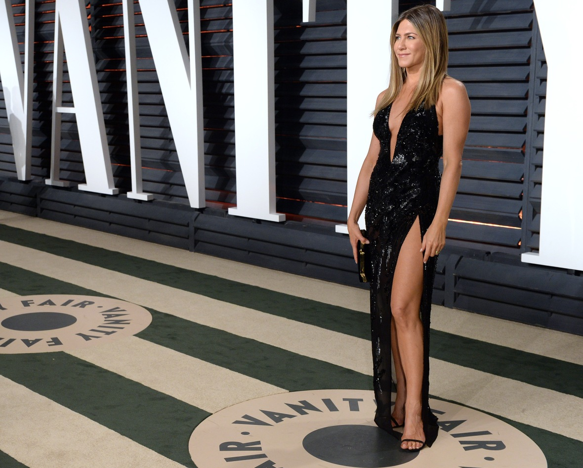 jennifer aniston in a black sparkly gown with thigh-high slit on the red carpet.