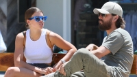 Scott Disick and Sofia Richie sitting on a bench talking