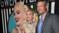 Gwen Stefani and Blake Shelton stand smiling on red carpet with photo of Gwen Stefani behind them