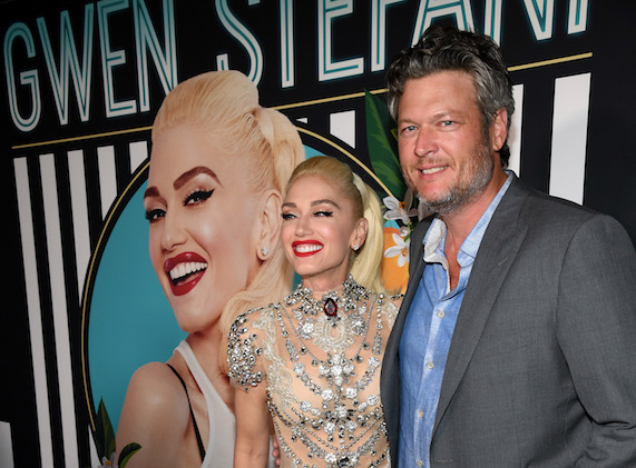 Gwen Stefani and Blake Shelton stand smiling on red carpet with photo of Gwen Stefani behind them