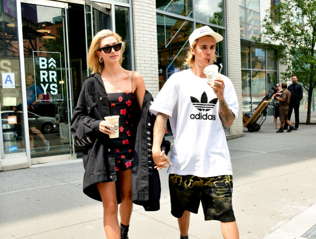 Justin Bieber and Hailey Baldwin holding hands near Barry's Bootcamp in NYC. Justin is drinking a smoothie and Hailey is wearing a black coat with a black dress