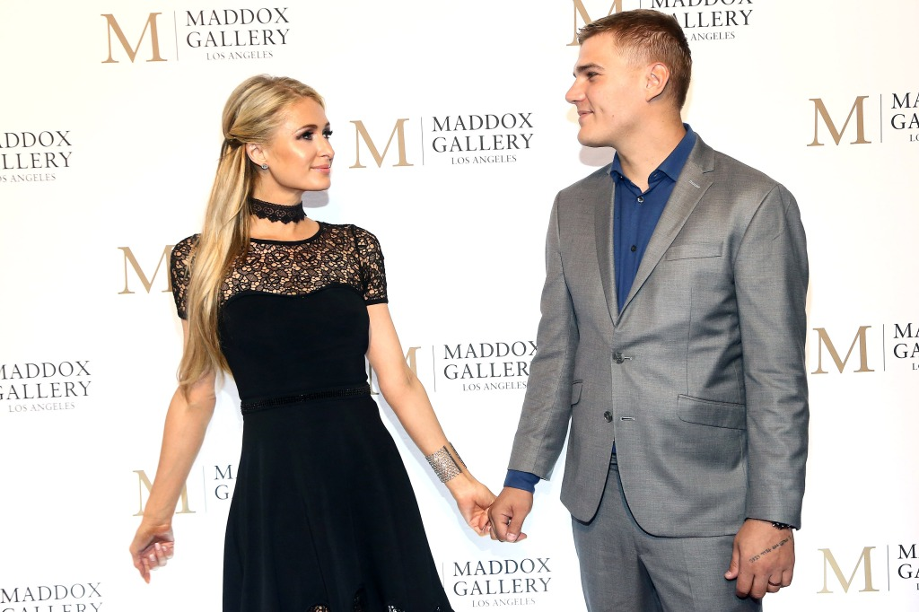 Paris Hilton, wearing black and Chris Zylka, wearing a gray suit holding hands at an event