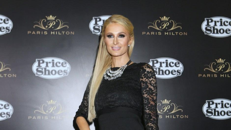 Paris Hilton wearing a lace dress, posing on a red carpet