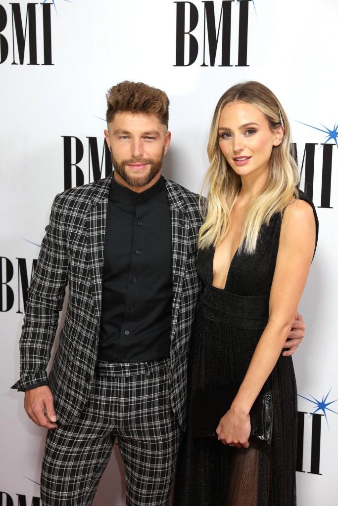 Lauren Bushnell in black dress standing with boyfriend country singer Chris Lane in plaid suit