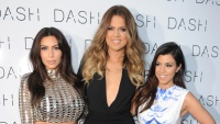 Kim Kardashian, Khloe Kardashian, and Kourtney Kardashian at an event. Kim wearing sequin dress, Khloe wearing black dress, and Kourtney wearing white and blue dress