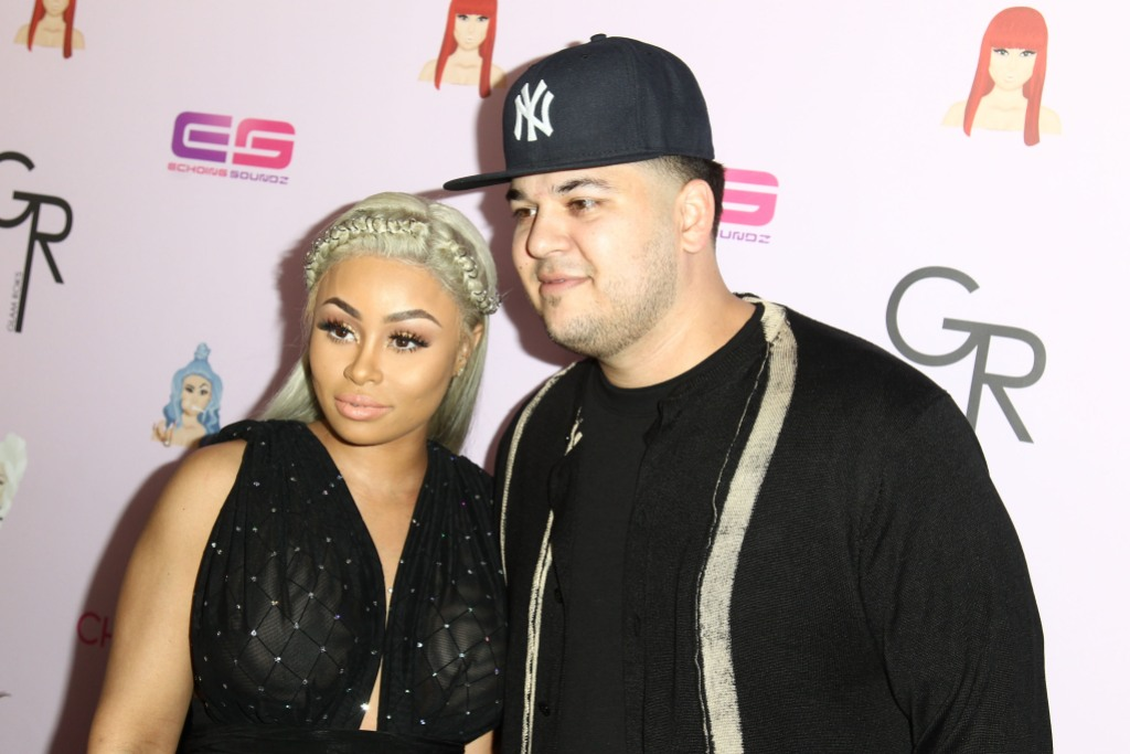 Blac Chyna, wearing black and Rob Kardashian, wearing black and in a hat pose on the red carpet together