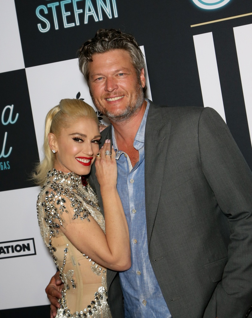 Gwen Stefani and Blake Shelton stand on red carpet smiling and hugging