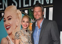 Blake Shelton and Gwen Stefani stand smiling with photo of Gwen behind them