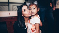 Kim Kardashian and North West at an Ariana Grande concert, wearing cat ears
