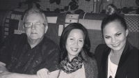 Chrissy Teigen with her mom and dad at a restaurant