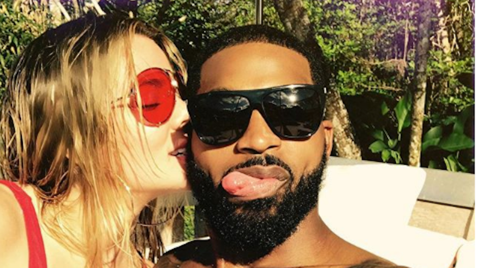 Khloe Kardashian wearing a red bathing suit with Tristan Thompson wearing glasses