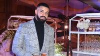Drake wearing a gray suit at New Year's Eve party