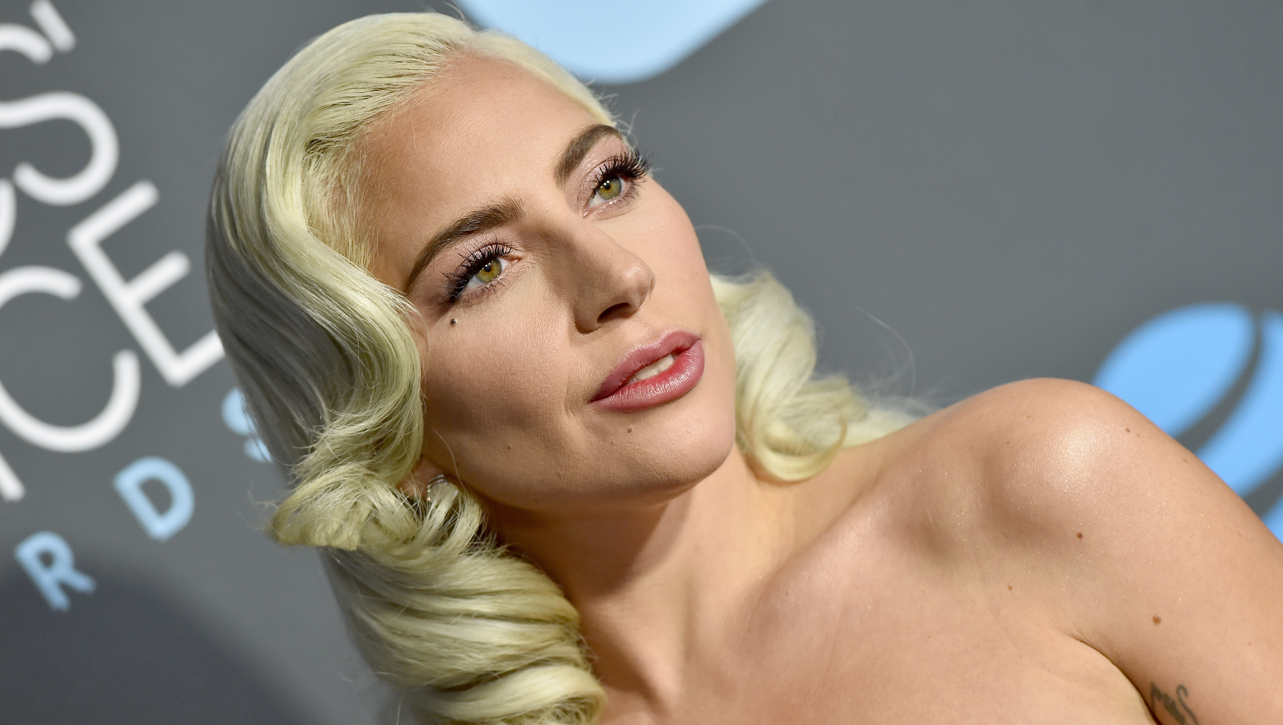 Upclose shot of Lady Gaga with curled blonde hair and a nude pink dress