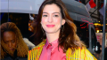 Anne Hathaway walking in NYC wearing a yellow plaid coat and coral dress