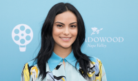 Camila Mendes smiling with her hair down wearing a blue yellow and black dress