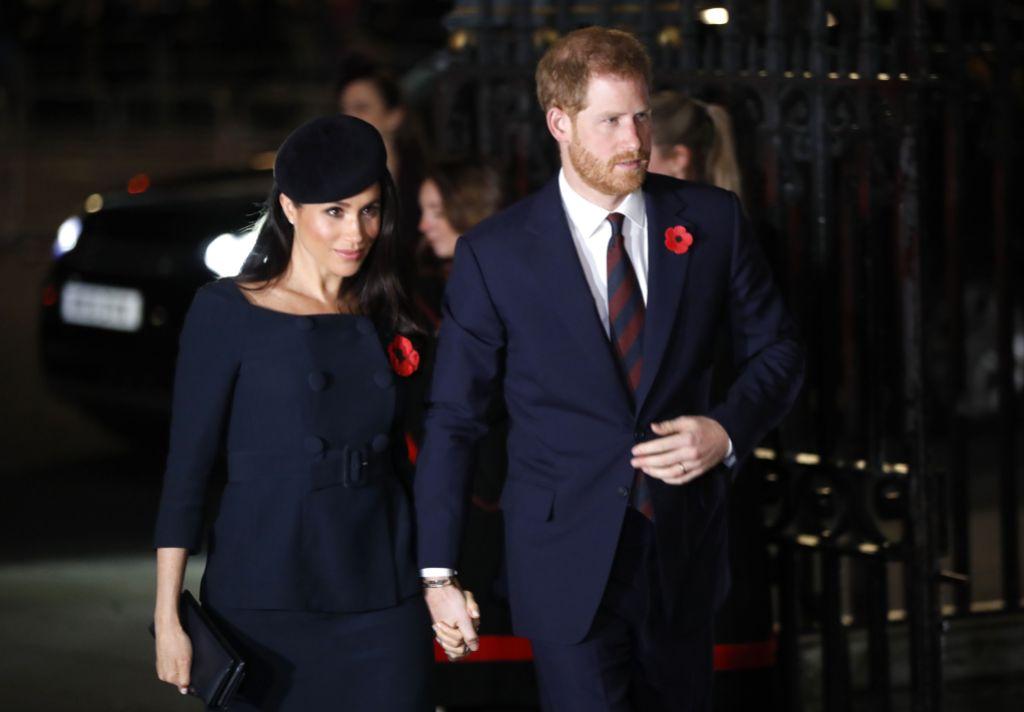 Meghan Markle wearing a dark blue dress with Prince Harry