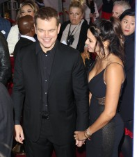 Matt Damon wearing a black suit holding hands with wife Luiciana