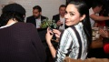 Vanessa Hudgens smiling with slicked back hair at a dinner table