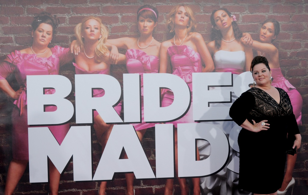 Melissa McCarthy posing in front of a Bridemaids poster