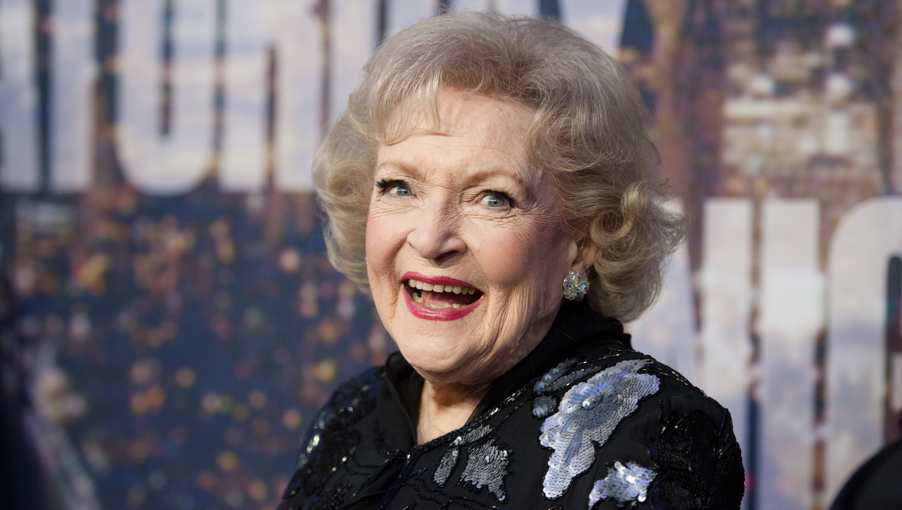 Betty White up close shot of her smiling in a black dress