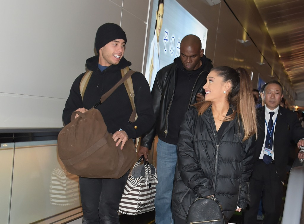 Ariana Grande Ricky Alvarez laughing in winter coats walking through the airport
