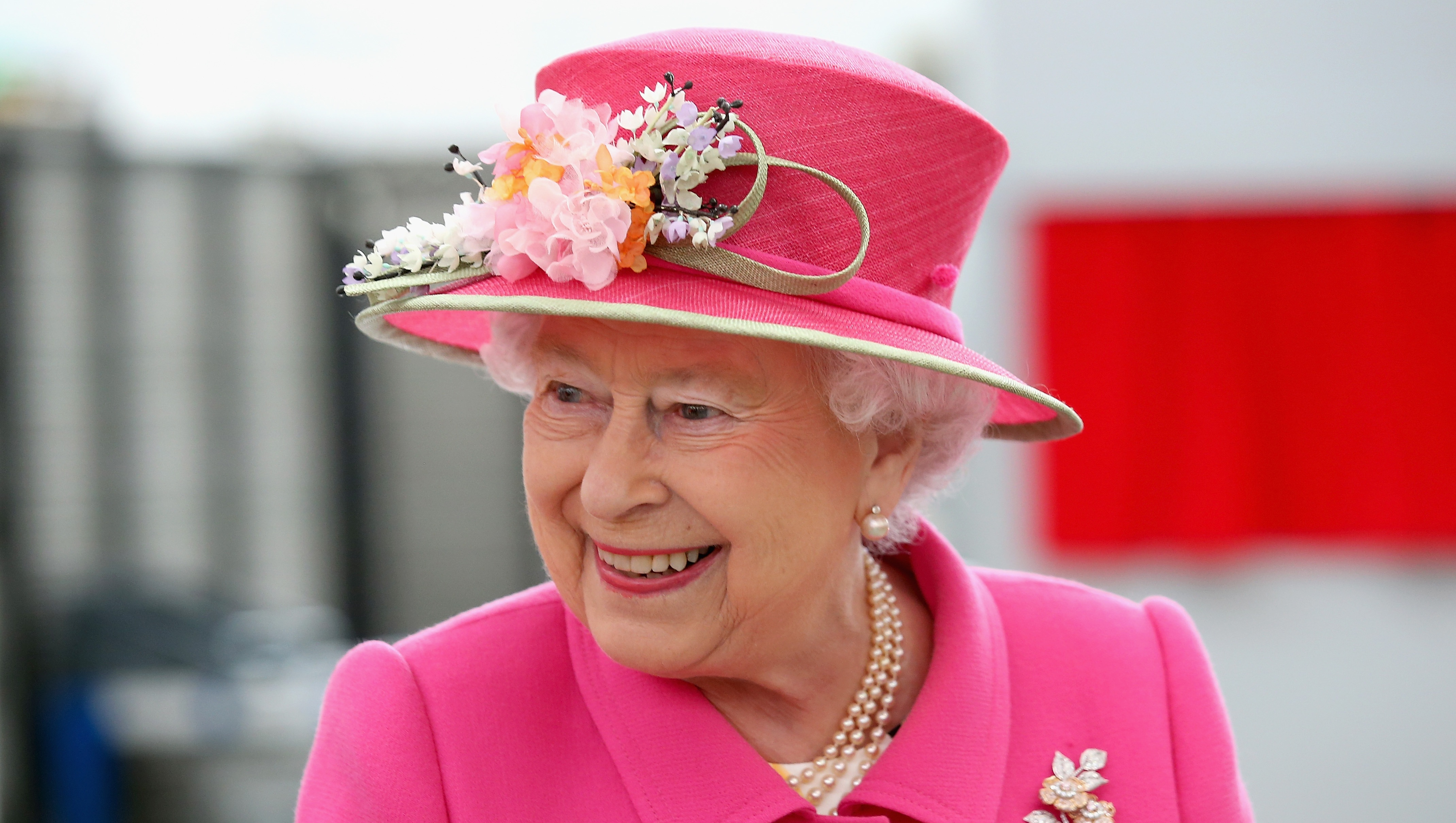Queen Elizabeth II smiling in a pink outfit and matching hat