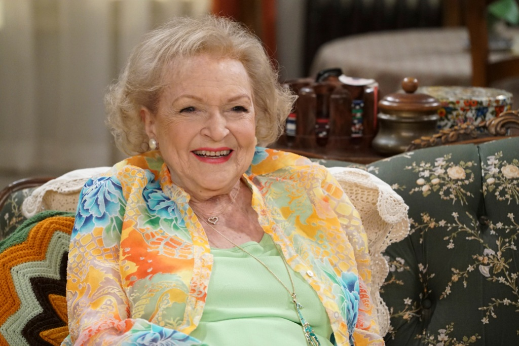 Betty White smiling wearing a floral blazer and green top