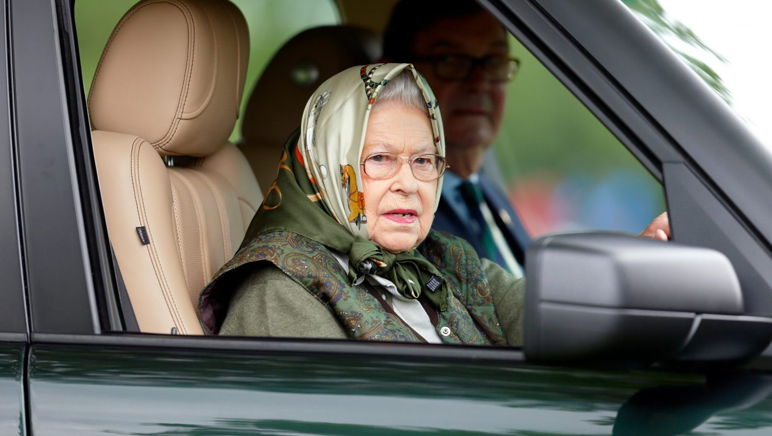Queen Elizabeth driving in her car with a head scarf on