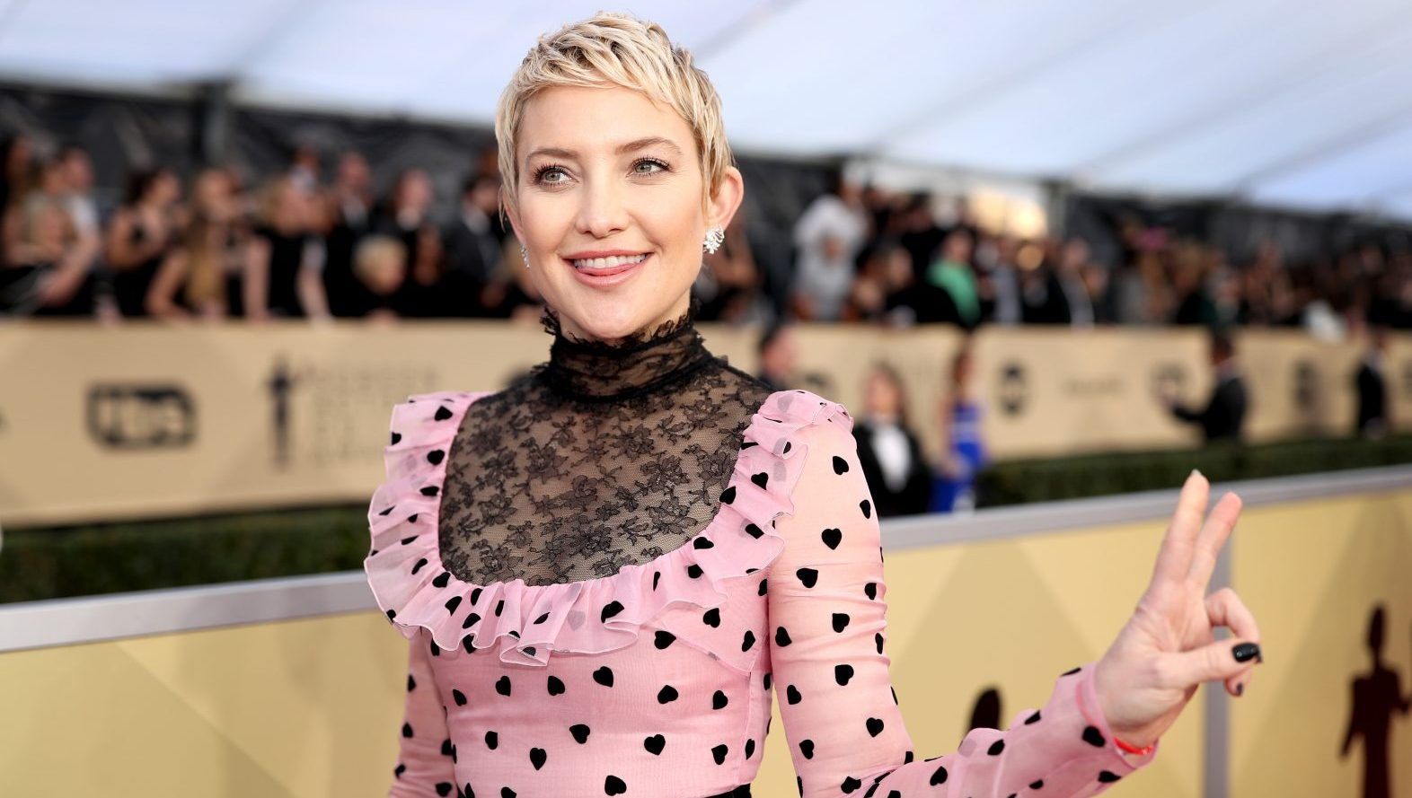 Kate Hudson giving a peace sign in a prink dress