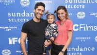 Nev Schulman, wearing all black with daughter and wife, Laura Perlongo, wearing an orange shirt at an event
