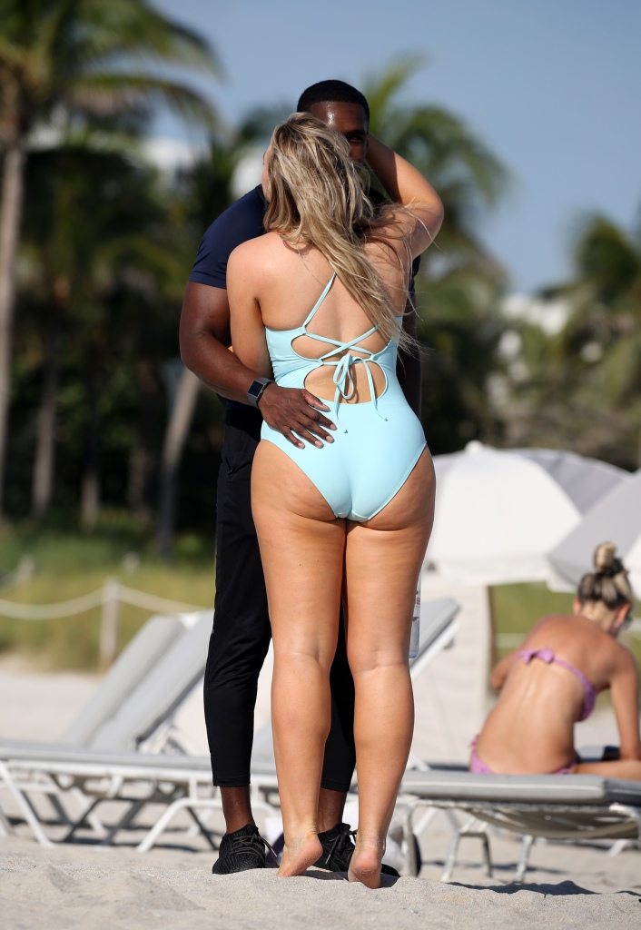 Model Iskra Lawrence greets her boyfriend with a big kiss while she poses in bikinis on the beach in Miami