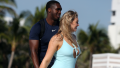 Iskra Lawrence walking with her boyfriend on the beach while wearing a blue bathing suit