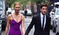 Karlie Kloss and husband Joshua Kushner walking down the street and holding hands, Karlie is wearing a purple dress and Joshua is wearing a black tuxedo