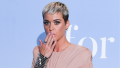 Katy Perry posing in a pink dress with her hand covering her mouth in shock