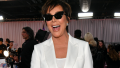 Kris Jenner smiling while wearing black sunglasses and a white pant suit