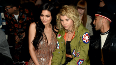 Kylie Jenner and Sofia Richie sitting together at New York Fashion Week in 2017, Kylie is wearing a sparkly gold dress and Sofia is wearing a green jacket with patches on it