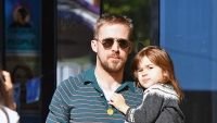 Ryan Gosling wearing sunglasses and carrying his daughter