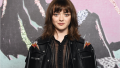 Maisie Williams posing in a black jacket with straight hair and bangs