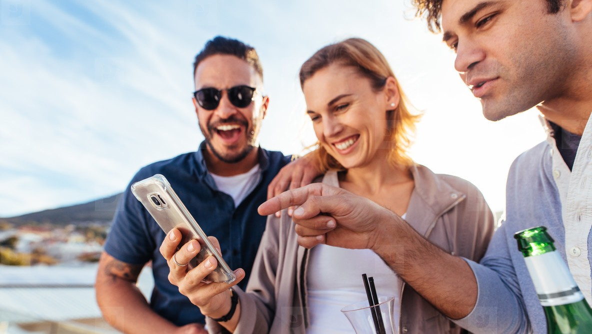 Three people crowded around a cell phone