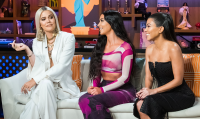 Khloe, Kim, and Kourtney Kardashian sitting on a couch during Andy Cohen's Watch What Happens Live