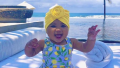 Khloe Kardashian's daughter True Thompson wearing a blue bathing suit with lemons on it