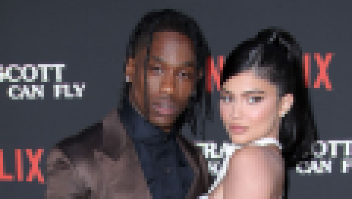 Kylie Jenner Wears White Dress While Hugging Travis Scott in Brown Suit