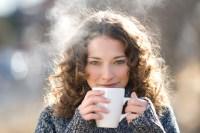 Brunette woman in pullover drinking hot tea