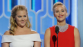 Amy Schumer and Jennifer Lawrence standing on stage