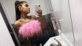 Ariana Grande taking a selfie in a fuzzy pink top