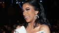 Cardi B smiling in a white dress at the 2019 Grammy Awards