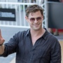 Chris Hemsworth wearing sunglasses, smiling and giving the peace sign