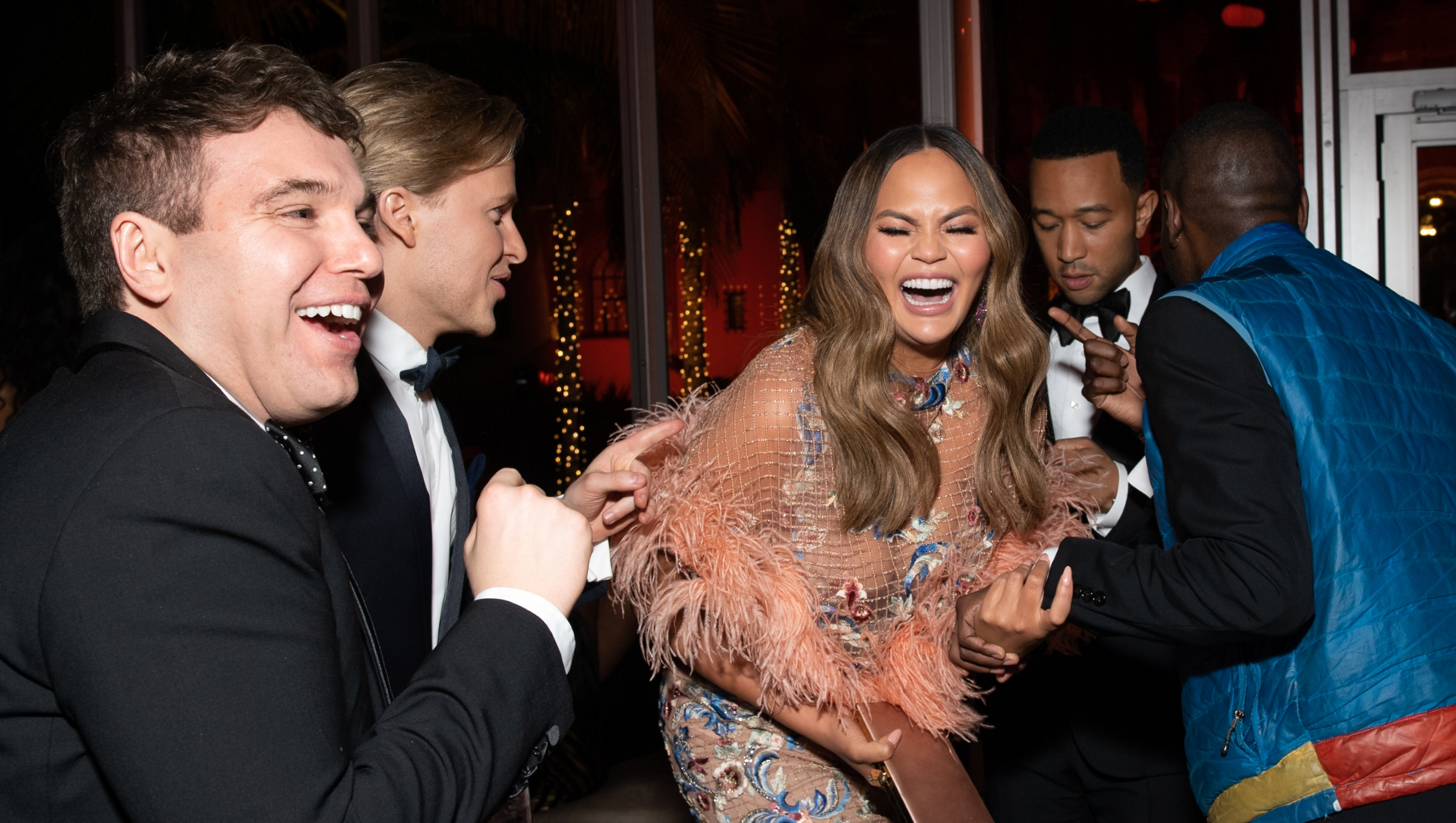 Chrissy Teigen laughing at the oscars wearing a pink dress
