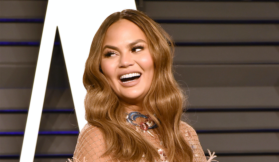 Chrissy Teigen looking over her shoulder and smiling at the 2019 Oscars